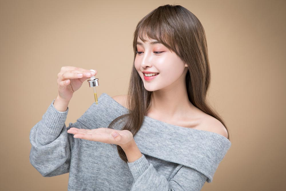 A fair-skinned woman is preparing to apply the serum to her face.