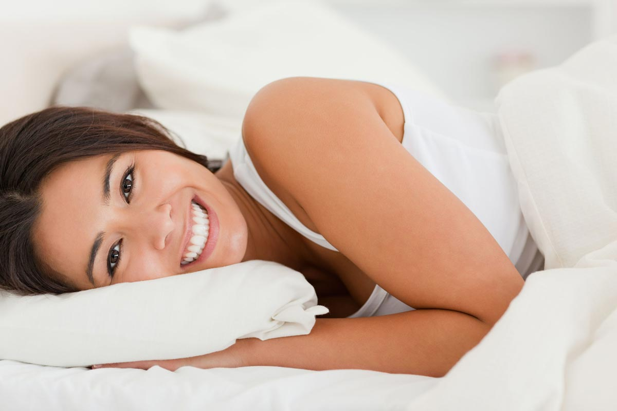 A beautiful woman is lying on the bed smiling at you.