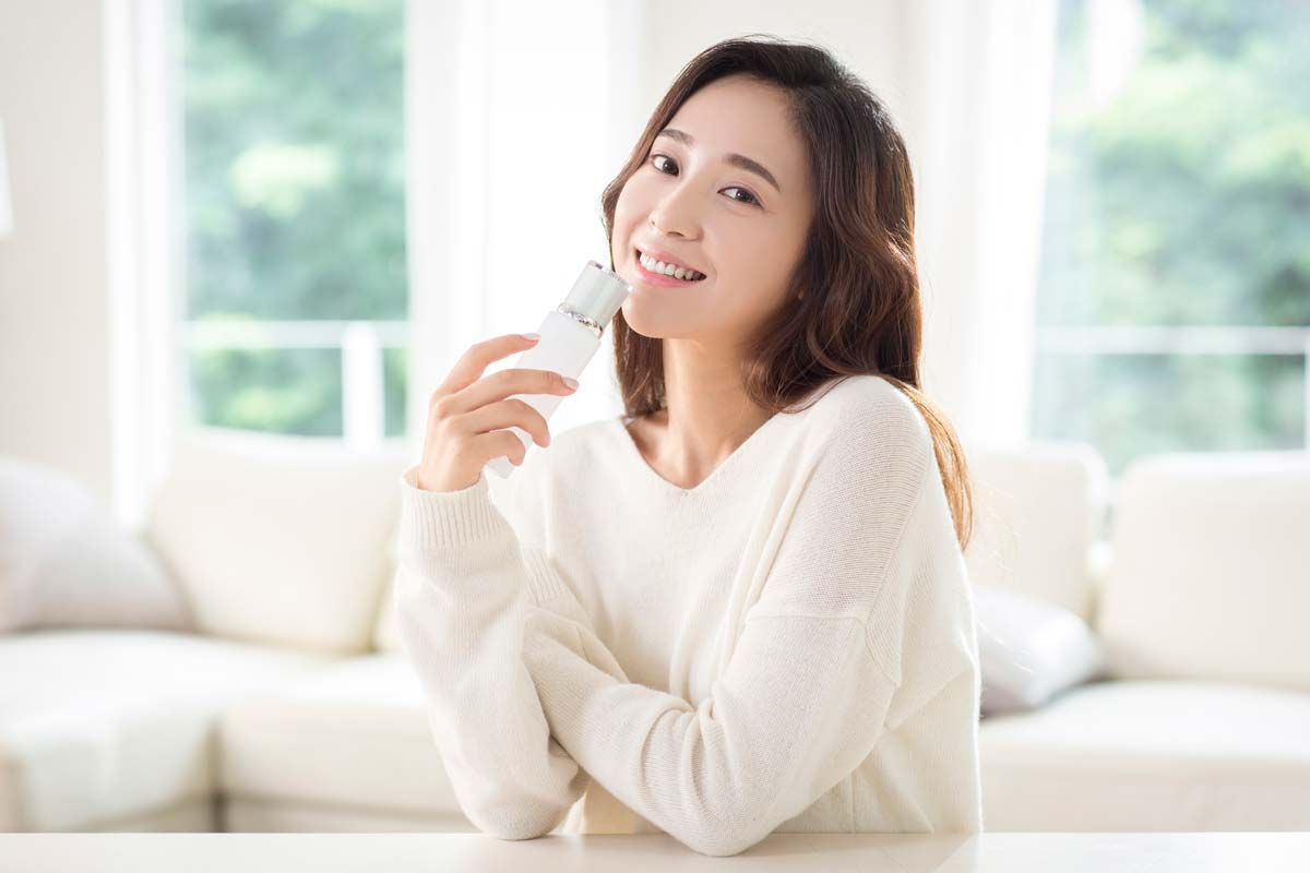 A beauty smiles while holding skin care products