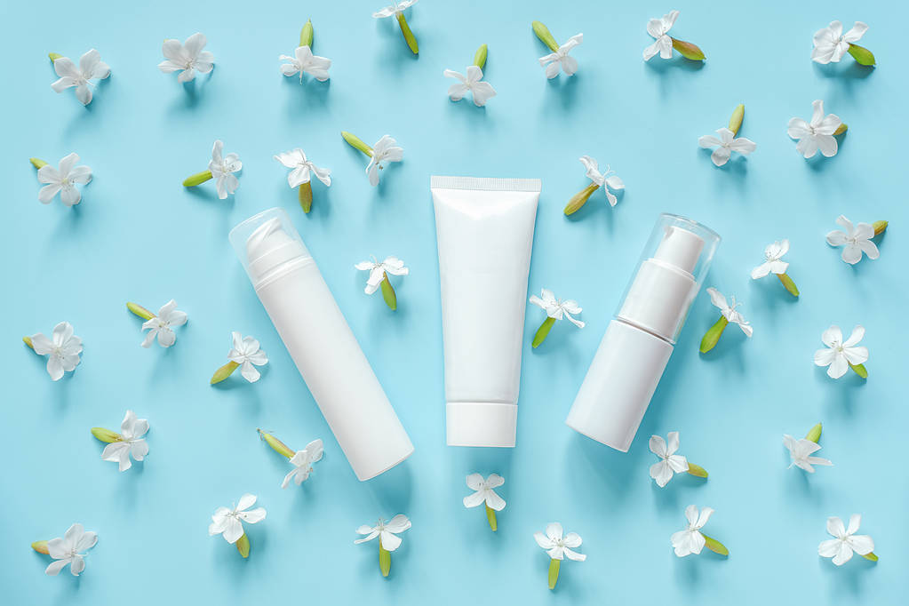 White flowers and three cosmetic, medical white tube, bottle for cream, ointment, toothpaste or other product on blue background. Concept natural organic cosmetics, homeopathic cosmetology Mockup